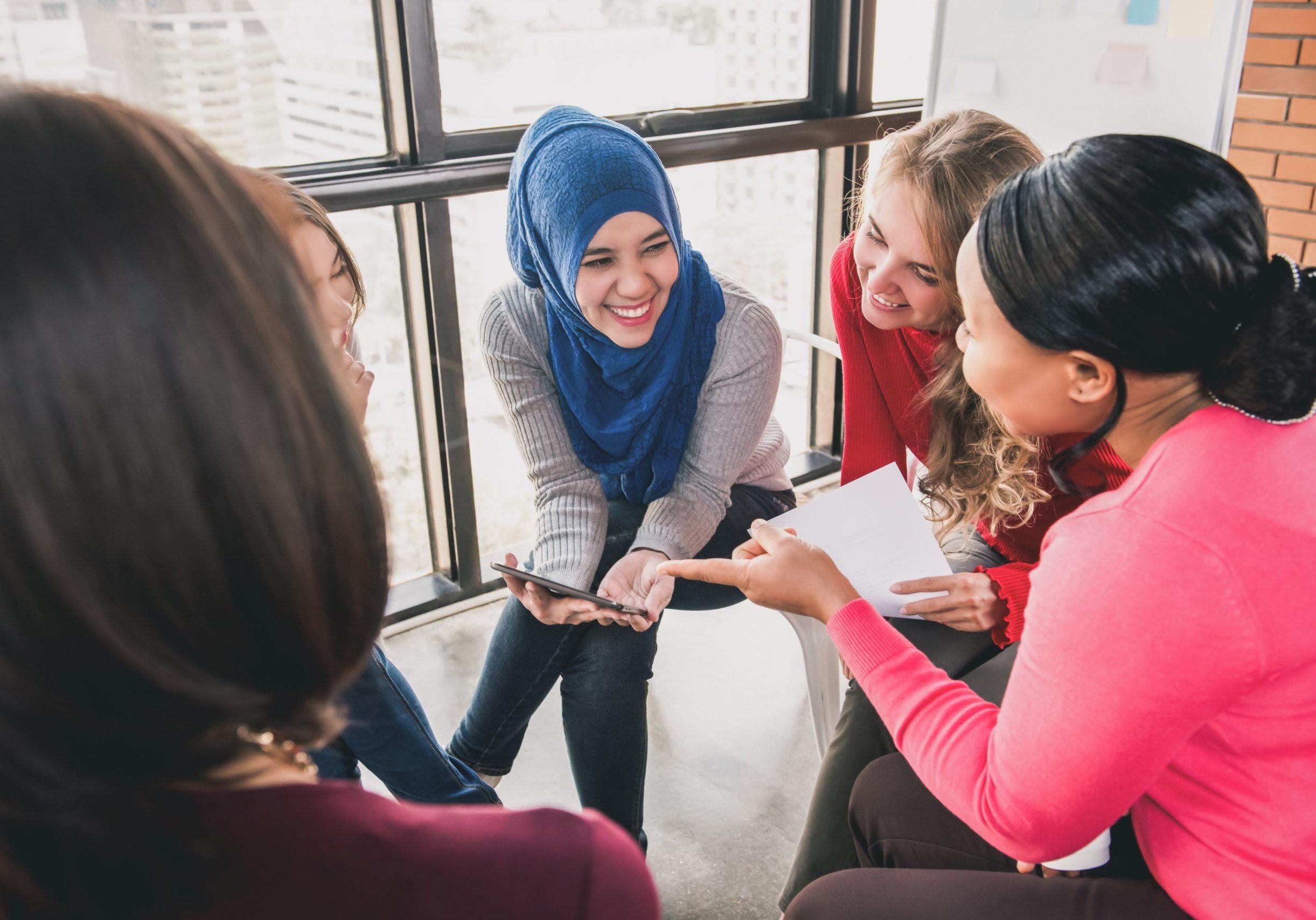Diverse women sitting in circle enjoying sharing stories in group meeting