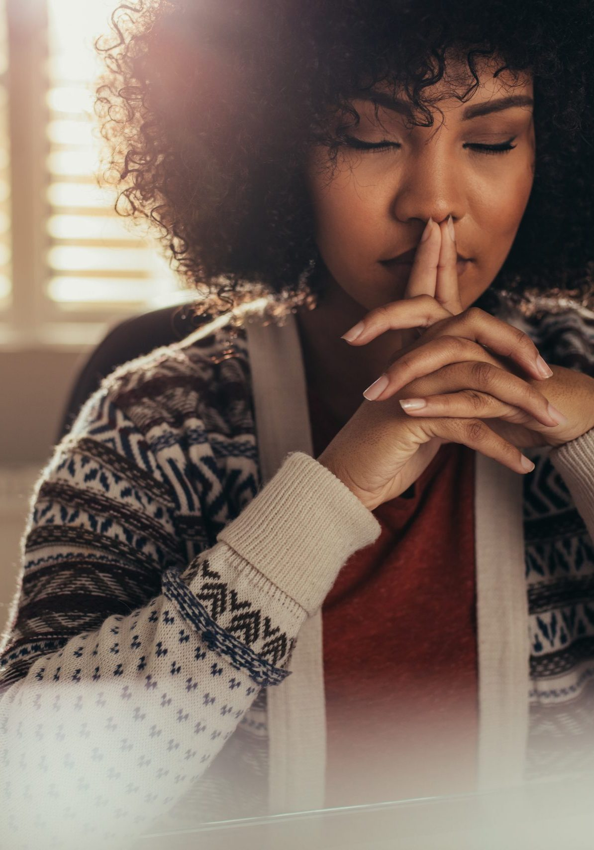 African female sitting at her work desk and thinking with her eyes closed. Stressed woman taking a break to come up with solution using mindfulness.