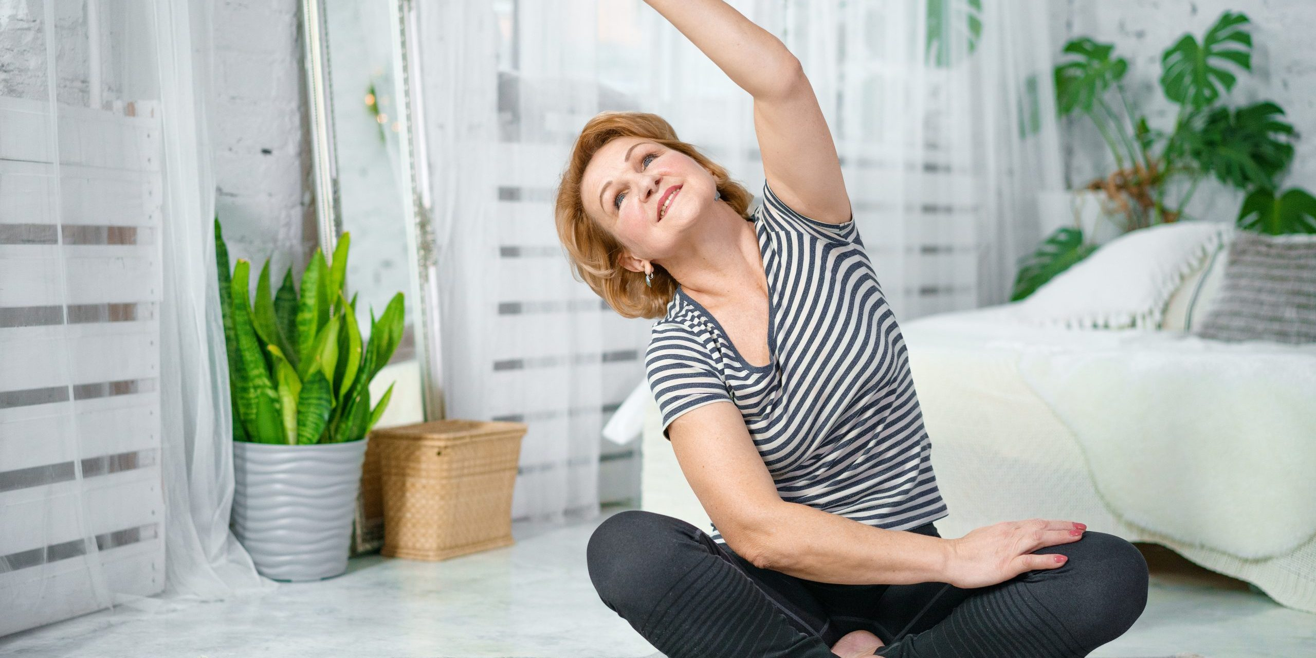 Senior woman exercising while sitting in lotus position. Active mature woman doing stretching exercise in living room at home.